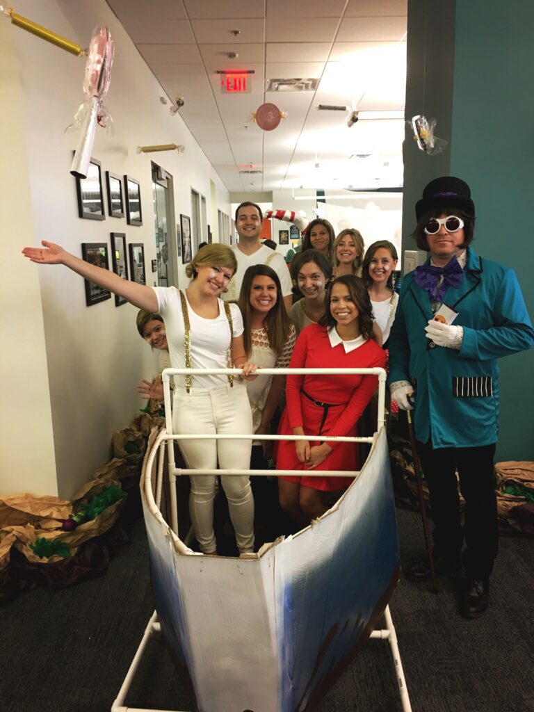 Photo of Katy Tipton, Candidate Experience Specialist at Aspireship, a SaaS sales training and job placement company; the photo shows her and her prior team at a halloween party.